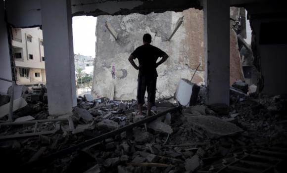 A Palestinian man looks at a destroyed house following an overnight Israeli missile strike in Gaza City Monday, July 14, 2014.  (Photo: AP/Khalil Hamra)