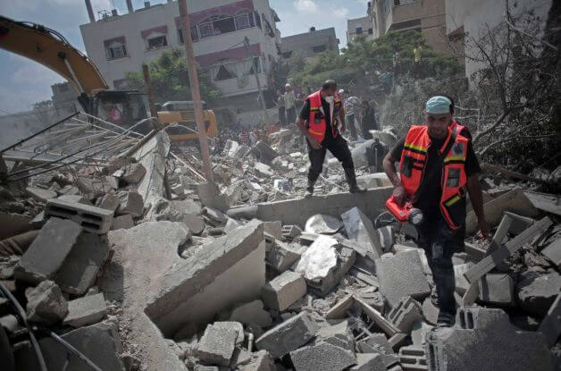 Palestinian rescue workers search for survivors under the rubble of a house was destroyed by an Israeli missile strike, in Gaza City, Monday, July 21, 2014. (Photo: Khalil Hamra/ AP)