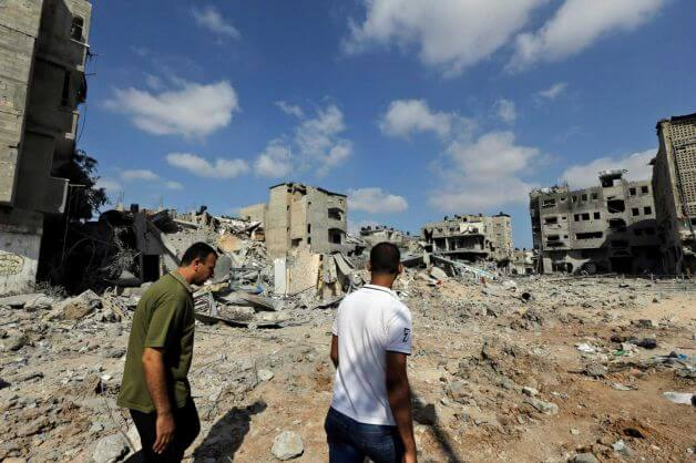 Palestinians walk past the rubble of houses destroyed by Israeli strikes in Beit Hanoun, northern Gaza Strip, Sunday, July 27, 2014. (Photo: Lefteris Pitarakis, AP)