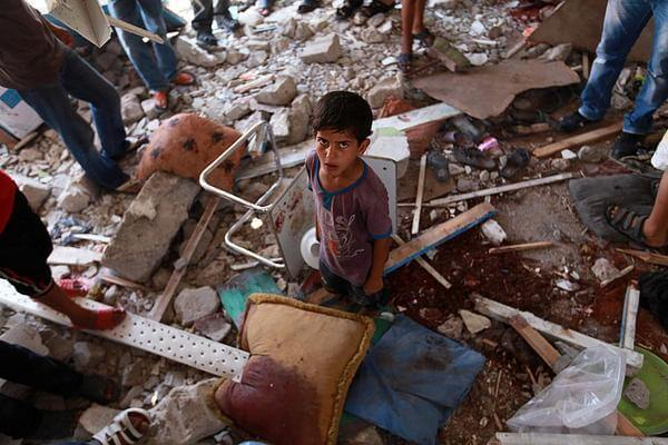 A child in the aftermath of the Israeli attack on an UNRWA school. (Photo: Reuters and EPA)