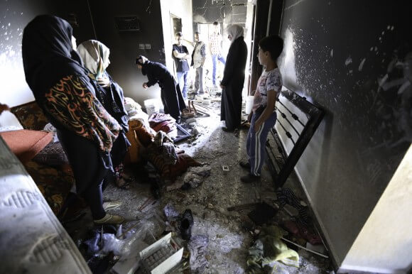 Family members and neighbors inspect the damage.  The Aisha family was kept inside during much of the raid until soldiers evacuated them outside to detonate the explosives. (Photo: Kelly Lynn)