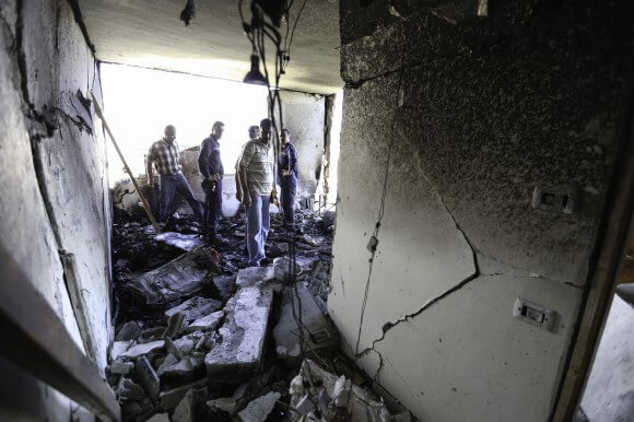 Neighbors and family members inspect the damage of the second floor living room after IDF set off explosives during the night. (Photo: Kelly Lynn)