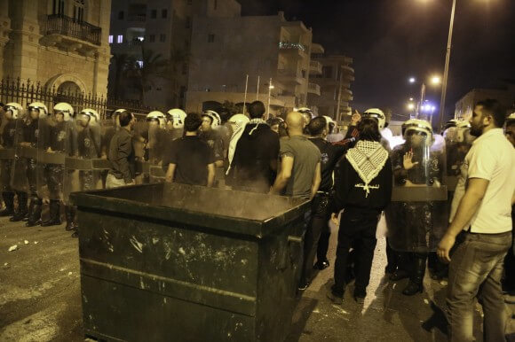 "A young protester pushes a dumpster toward the PA barricade yelling, ""hezbalah,"" trash in Arabic. (Photo: Kelly Lynn)"