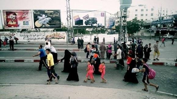 Palestinians in Shuja'ieyh neighborhood fleeing from Israeli shelling and gunshots earlier this morning. (Photo: Lazar Simeonov)