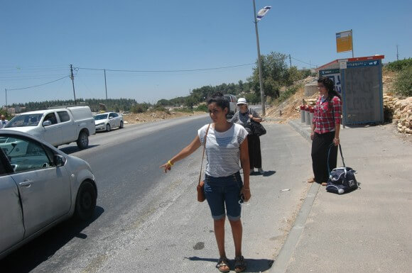 Israelis hitchhiking at the spot where the three youths were abducted in the Gush Etzion settlement bloc, on the day of the teens's memorial. (Photo: Allison Deger)