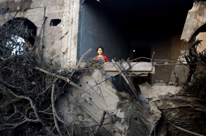 A Palestinian girl stands in a destroyed building following an Israeli military strike in  Gaza City on July 08, 2014. (Photo: AFP PHOTO / MAHMUD HAMSMAHMUD HAMS/AFP/Getty Images)