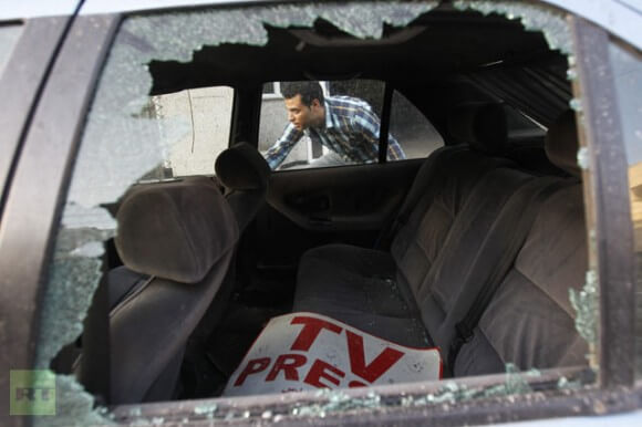 A Palestinian journalist inspects his work car in Gaza City on November 18, 2012.