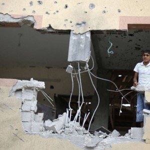 Palestinians look out of their house, which witnesses said was damaged during the Israeli offensive, on the fourth day of a five-day ceasefire in Johr El-Deek village near the central Gaza Strip August 17, 2014. (PHOTO: REUTERS, Ibraheem Abu Mustafa)