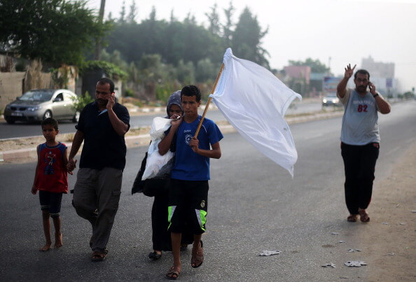 Palestinians fleeing Khan Yunis  hold white flags.(Photo: Belal Khaled/Anadolu Agency/Getty Images)
