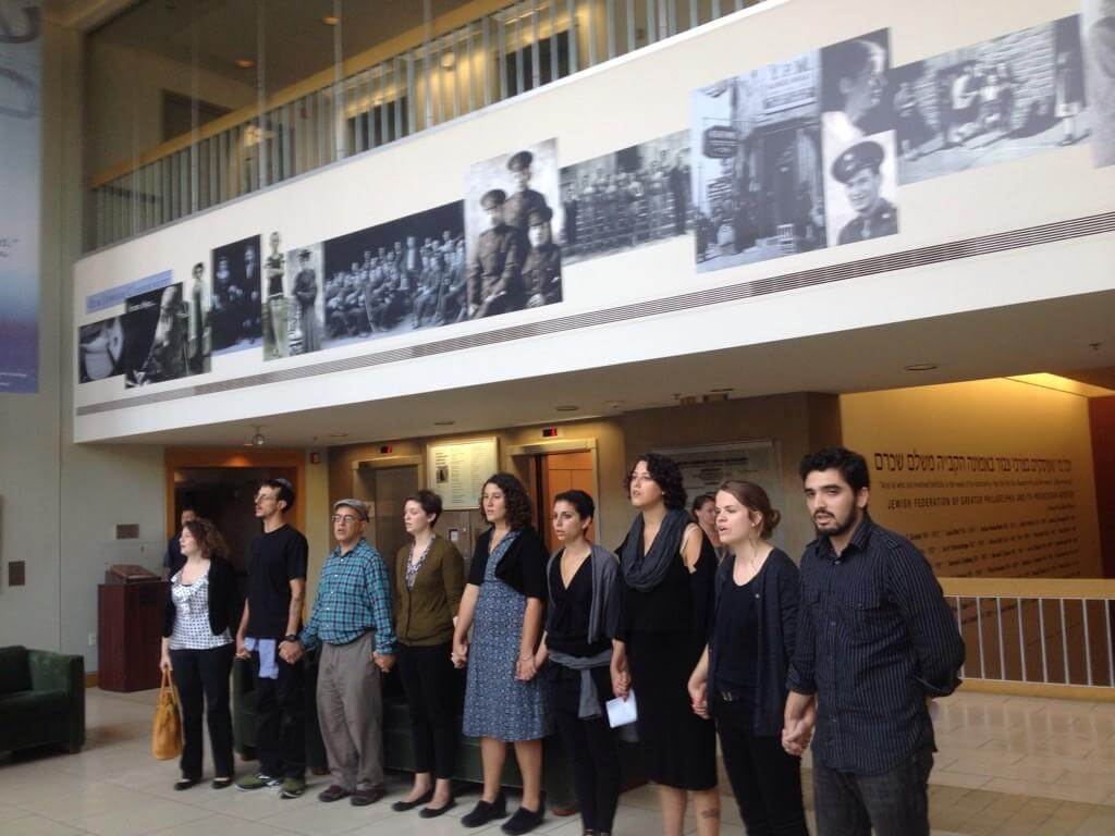 Demonstrators under a photo display at the Federations offices