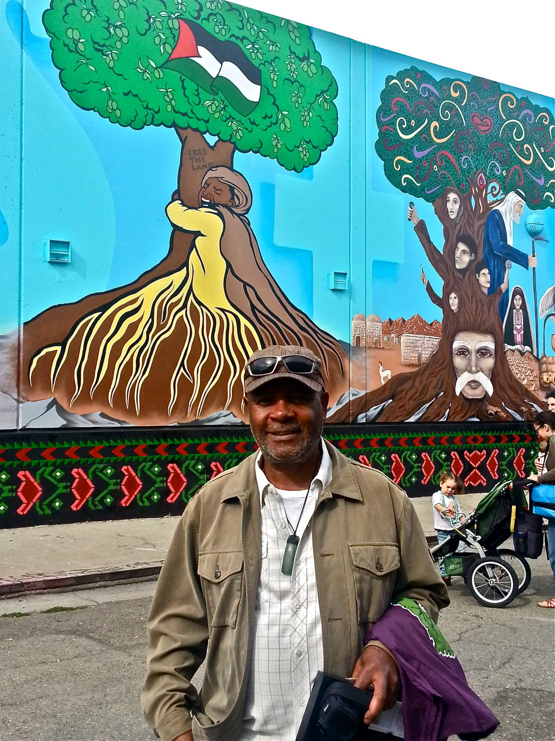 Emory Douglas, renowned former illustrator for The Black Panther newspaper, in front of the panel he contributed to the mural. (Photo: Henry Norr)