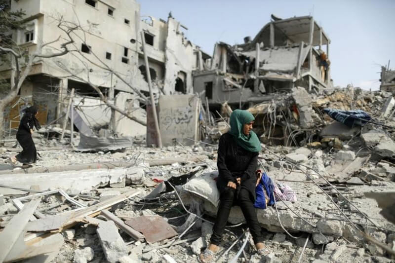A Palestinian woman sits on the remains of her destroyed house after returning to Beit Hanoun town. (Photo: Reuters)