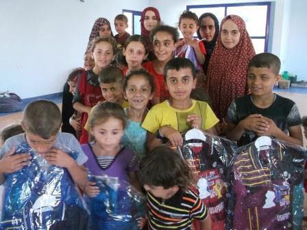 Refugee children from northern Gaza receiving aid from Palestine Children's Relief Fund