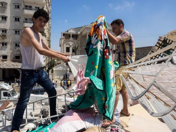 Assad Saftawi and his cousin stuff blankets into a bag. (Photo: Dan Cohen)