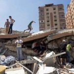 Young men look for their belongings in the remnants of a Gaza apartment building, August 2014. (Photo: Dan Cohen)