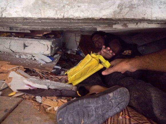 A Gazan man climbs deep into the rubble to recover belongings. (Photo: Dan Cohen)