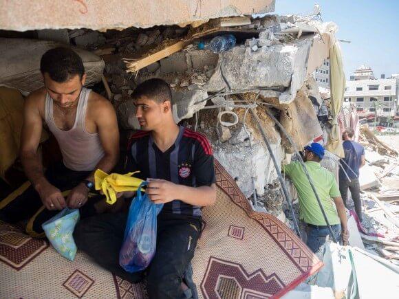 Men search through the destruction of their respective homes. (Photo: Dan Cohen)