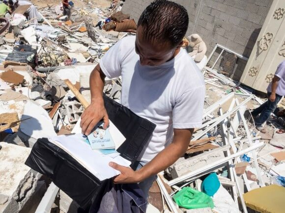 "A man finds medical records including a booklet entitled ""Mother and Child Health Handbook"" (Photo: Dan Cohen)"