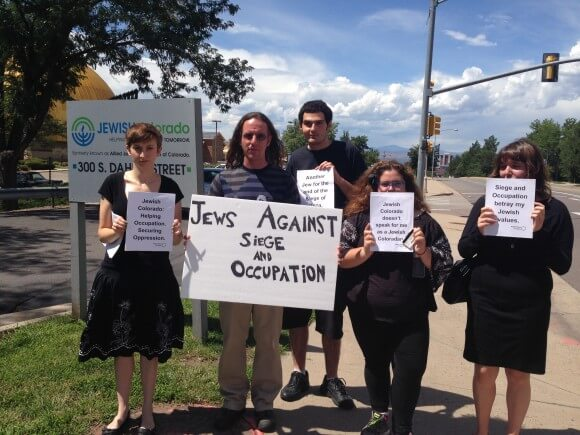 Front Range JVP activists who tried to deliver the petition to the office of JEWISHcolorado pictured here after the action with the JEWISHcolorado sign and the signs they used during the action. left to right, Abby Harms is the woman on the far left wearing the skirt, next to her (the only one not in black) is Evan Herzoff, next to him (towards the back) is Neal Feldman, next to him is me, Julia Wedgle and next to me, on the far right is Zoe Handler.