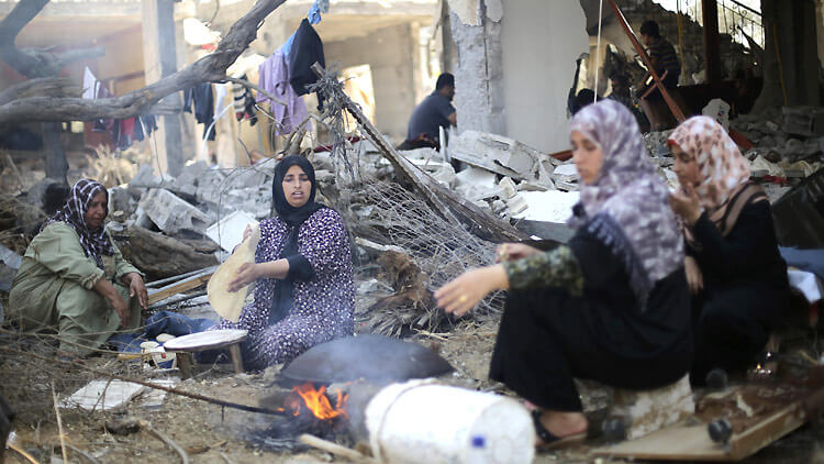 14 August 2014. Palestinian women bake bread in front of the remains of their house in Khan Younis, in the southern Gaza Strip. (Photo: Reuters/I. Abu Mustafa via ICRC)