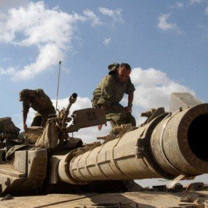 Israeli soldiers stand on top of a Merkava tank stationed at an army deployment area along the Israeli border with the Gaza Strip on July 26, 2014.  (Photo: GIL COHEN-MAGEN/AFP/Getty Images)