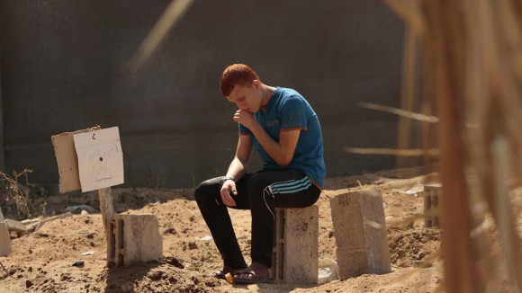 Carolyn Cole photo for LA Times of boy mourning a friend in makeshift graveyard in Gaza