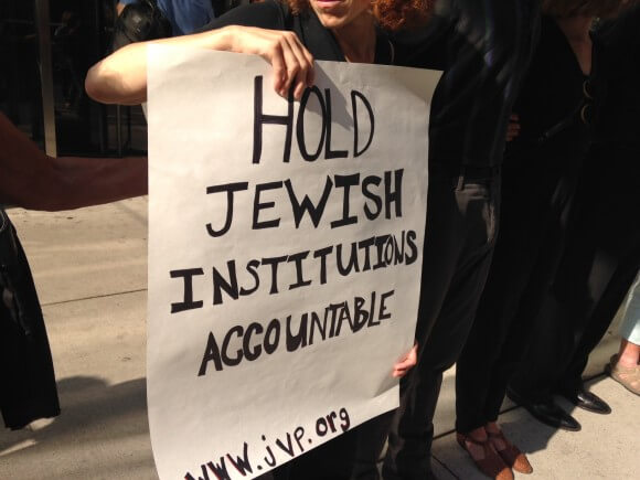 A sign held outside the UJA-Federation building. (Photo: Alex Kane)