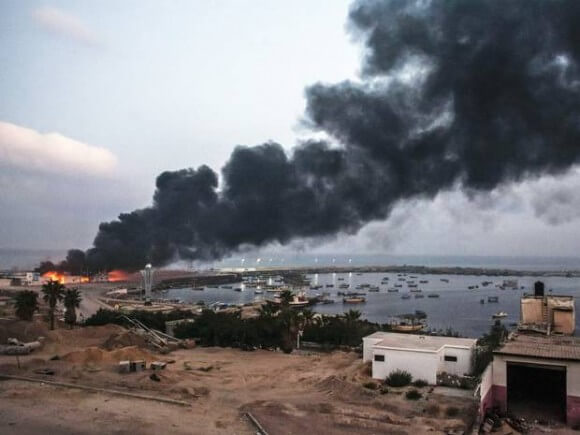 A building within the Gaza port is seen on fire after several strikes. (Photo: Getty Images)