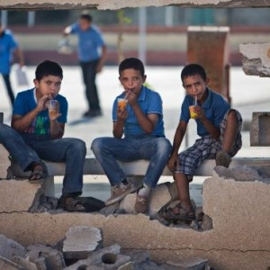 Palestinian school boys drink iced juice as they sit on a damaged wall of a school in Gaza City's Shujaiyeh neighborhood, Sunday, Sept. 14, 2014. (Photo: AP)