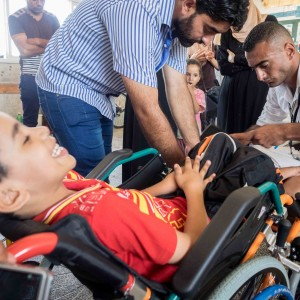 Usama Abu Safer helps assemble Mohammed Abu Maghseeb's wheelchair. (Photo: Dan Cohen)