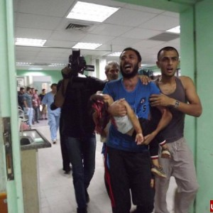 Saher's father crying and carrying him into the hospital
