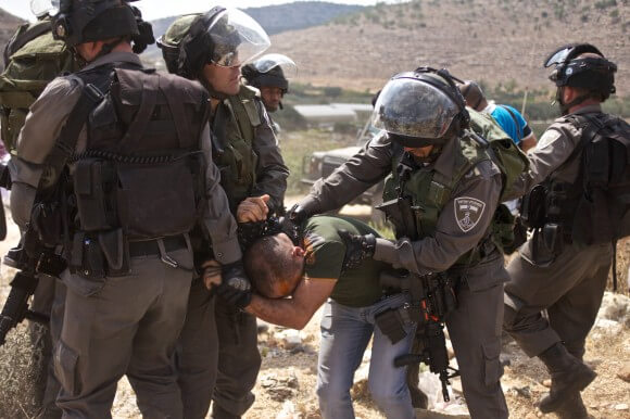 An activist is detained by Israeli border police after being pepper sprayed.  He was released shortly after. (Photo: Kelly Lynn)
