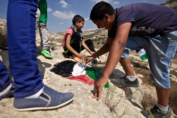 """Boys paint a Palestinian flag on a hillside set to be appropriated as Israeli """"state land."""" (Photo: Kelly Lynn)"""