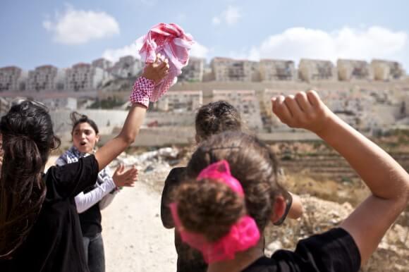 Teenage girls chant toward the settlement of Beitar Illit following Wadi Fukin's Friday demonstration on September 12th.  (Photo: Kelly Lynn)