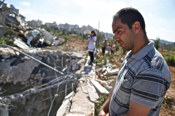 Ataef Al Jabari, a worker employed by the factory looks into the demolished well. (Photo: Kelly Lynn)
