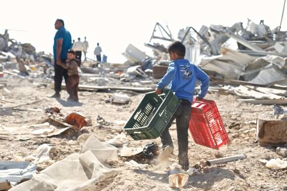 Kamal Al Jabari walks with his two sons as they help to salvage what is left. (Photo: Kelly Lynn)