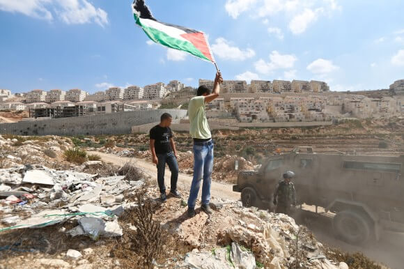 An activist waves a Palestinian flag in front of Beitar Illit as additional military vehicles arrive to repress the demonstration. (Photo: Kelly Lynn)