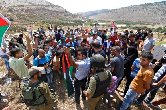 Ahmad Sukar, head of the village council holds a Palestinian flag during Wadi Fukin's first Friday demonstration shortly before he was pepper sprayed. (Photo: Kelly Lynn)
