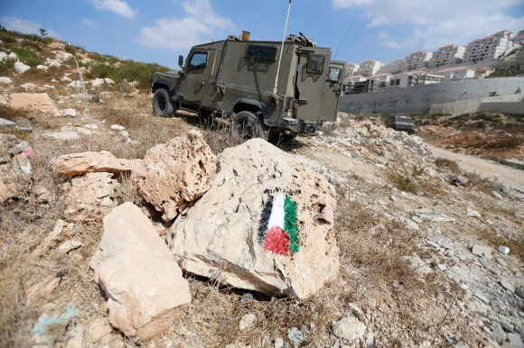 A military jeep parked on the hillside after the first Friday demonstration.  Activists painted Palestinian flags on rocks after Israeli authorities removed a flag previously planted by young activists. (Photo: Kelly Lynn)
