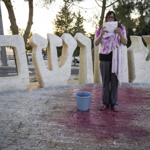 JAG activist Neta Golan recites a memorial statement in front of Yad Vashem, Jerusalem's holocaust museum after dowsing herself in fake blood. (Photo: Kelly Lynn)
