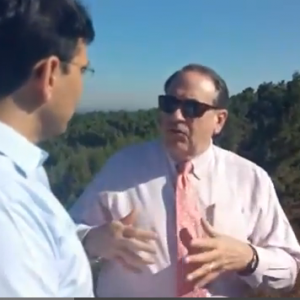 Mike Huckabee (right) speaks with Likud's Danny Danon in territory Israel annexed into the Gush Etzion settlement bloc on Sunday, September 7, 2014. (Screenshot of a video by Israel National News)