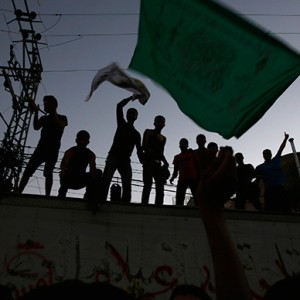 A Palestinian waves a Hamas flag (R) as others celebrate following a ceasefire in Gaza City August 26, 2014 (Reuters / Suhaib Salem)