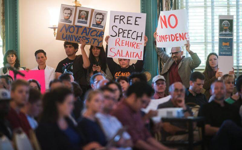 Protesters hold signs during the University of Illinois faculty senate meeting at the Illini Union Ballroom in Urbana on Monday, September 22 , 2014. (Photo: Robin Scholz/The News-Gazette)