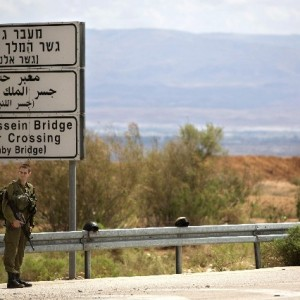 An Israeli soldier stands at the entrance of the King Hussein Bridge border crossing, the main border crossing for Palestinians from the West Bank traveling to Jordan in March, 2014 (AP photo)