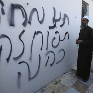 "Hebrew graffiti spray-painted on a wall at the entrance of a mosque that had been set alight in the West Bank village of Aqraba, near Nablus October 14, 2014. The graffiti reads, ""Price tag. Tapuah is Kahane"".   (Photo: REUTERS/Abed Omar Qusini)"