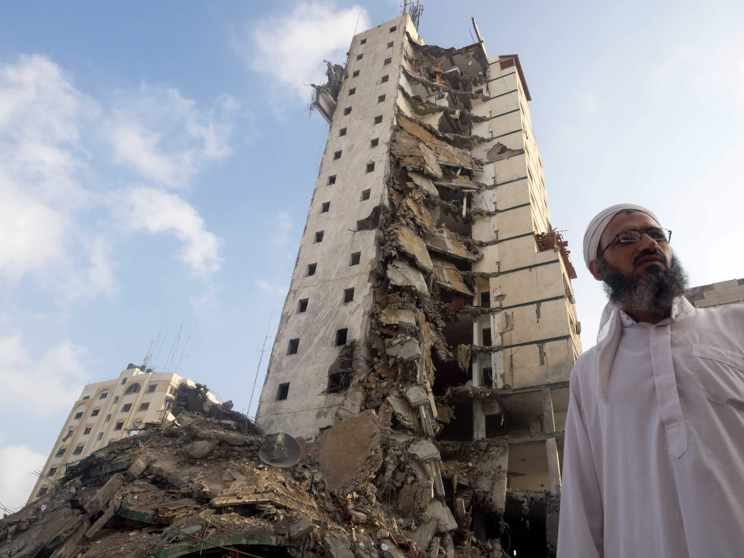 A resident of the Italian Compound stands in front of the destroyed building. (Photo: Dan Cohen)