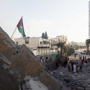 Palestinians planted a flag on the collapsed Basha tower as the sun rose. (Photo: Dan Cohen)
