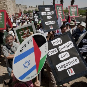 "Israeli and Palestinians take part in a rally to voice support for U.N. recognition of a Palestinian state, in Jerusalem this week. The banners read in Hebrew and Arabic ""Together we march for liberation,"" Jerusalem, 2011. (Photo: AP)"