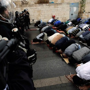 Palestinians pray as Israeli police officers stand guard during Friday prayers in the East Jerusalem neighbourhood of Wadi al-Joz on Oct. 31, 2014. (Photo: Reuters)