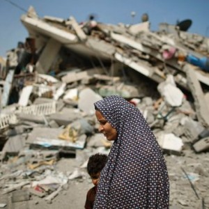 A Palestinian woman walks past the rubble of a residential building, which police said was destroyed in an Israeli air strike, in Gaza City, July 22, 2014. (Photo: Reuters)